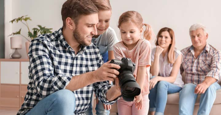 Photographer showing a little boy and girl photos on his camera, while the children's parents sit in the background