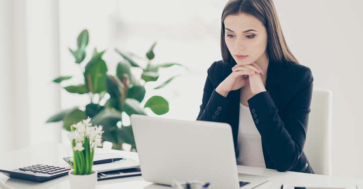 Woman in office sitting at desk resting chin on folded hands looking at laptop