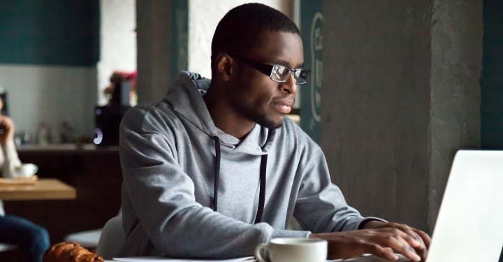 Man in gray sweatshirt types at laptop at desk with mug of coffee next to it