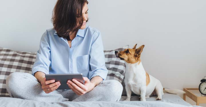 Cross-legged woman on bed looks down fondly at small dog while holding iPad