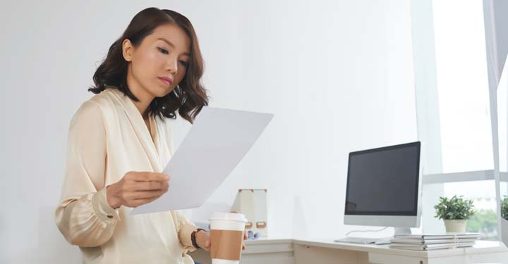 Woman with stylish bob looks at sheet of paper while holding disposable coffee cup with desk in background