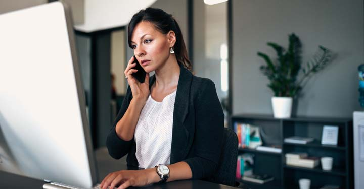Businesswoman in an office talking on a cellphone and using a desktop
