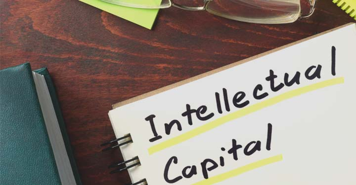 """An open notebook with the words """"Intellectual Capital"""" written inside next to a book and a pair of glasses"""