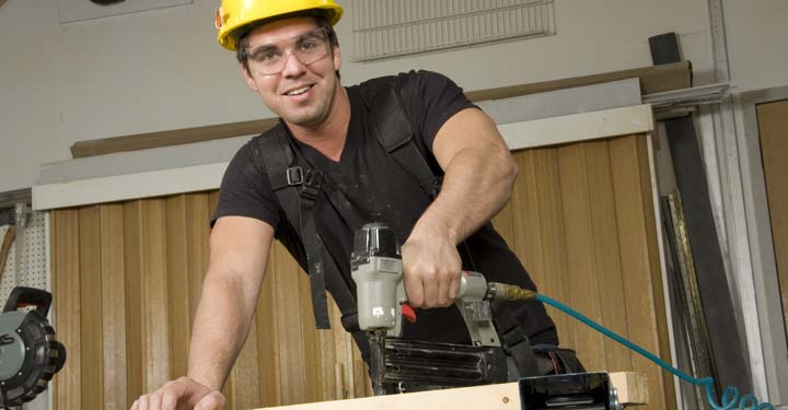 Construction worker in a hardhat and goggles holding a nail gun on a plank of wood