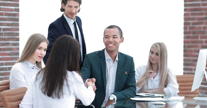 Coworkers in an office shaking hands