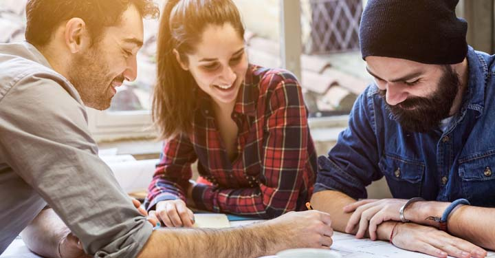 Three casually dressed hipsters laugh while signing documents