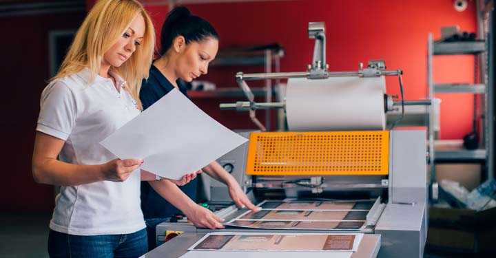 Blonde woman looking at image coming out of machine producing images as second woman stands behind her