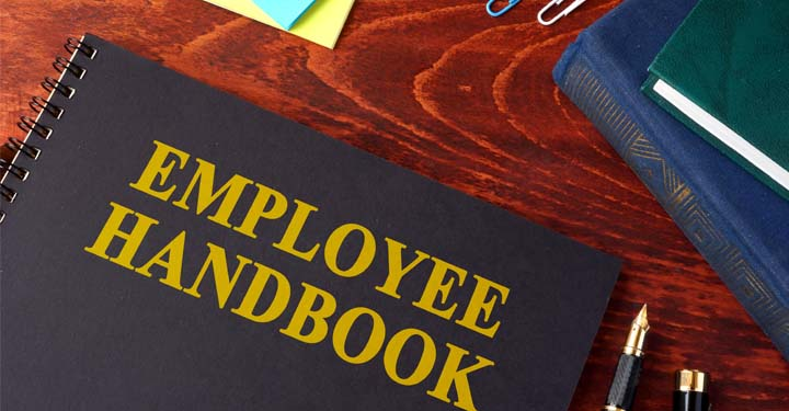 "A book whose cover reads ""Employee Handbook"" sitting on a table surrounded by office supplies"