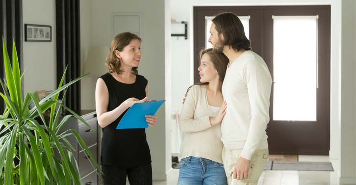 Woman and couple standing in a home reviewing paperwork