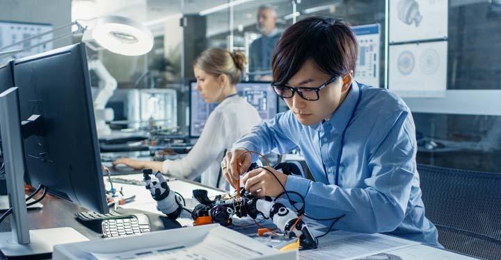 Man uses tools to adjust machine at desk in front of desktop computer