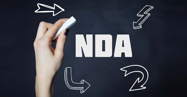 """Hand holding a piece of chalk on a black backdrop with white letters spelling """"N.D.A."""""""