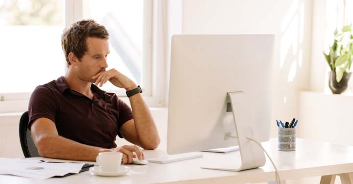 Man with mustache sitting at desk at desktop computer with coffee mug