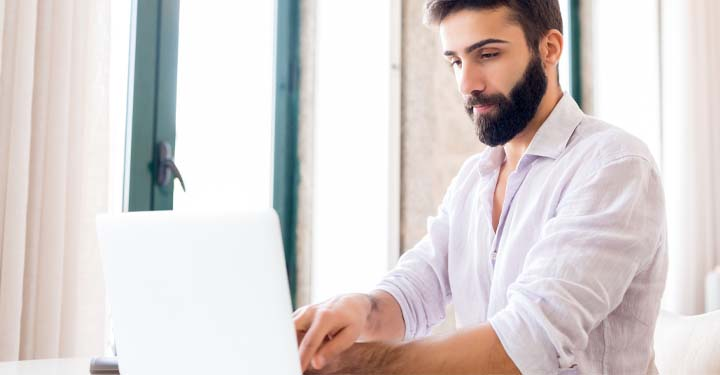 Bearded man typing at laptop with shirt pushed up to elbows