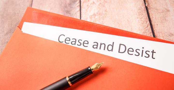 """Fountain pen on orange folder containing paper with title """"cease and desist"""" printed on it"""