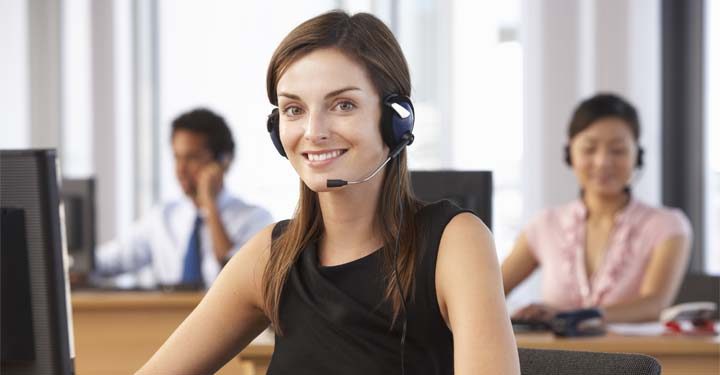 Woman in headset in front of computer smiles while listening to customer