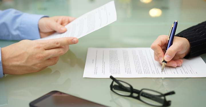 Hands holding a paper and another hand signing a document across the table