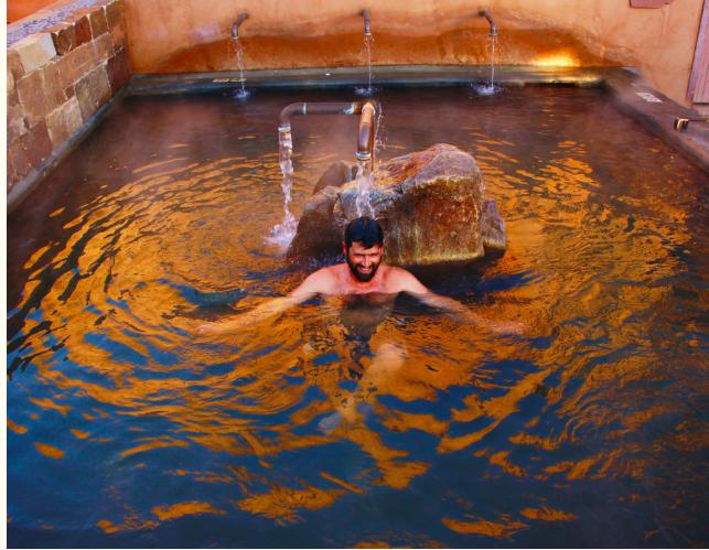 man in a hot springs bath at Ojo Caliente Mineral Springs Resort & Spa