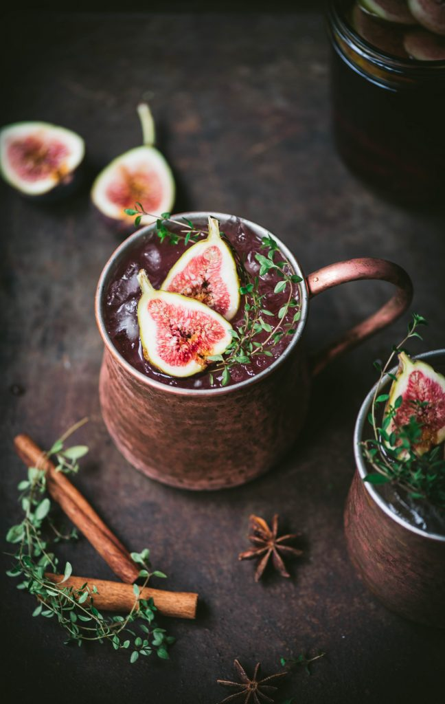 2 mugs of Fig Moscow Mule fall cocktail with cinnamon sticks and figs around them