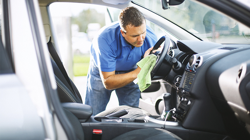 man cleaning a steering wheel