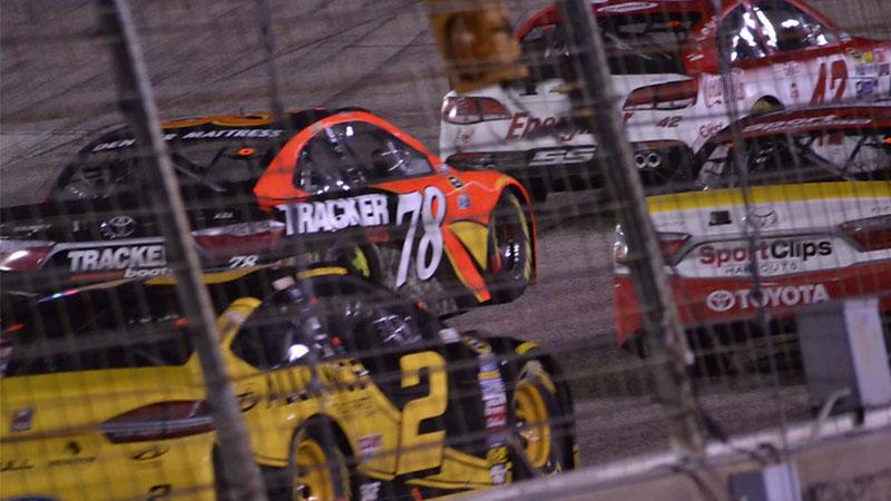 close-up of a NASCAR race through a fence