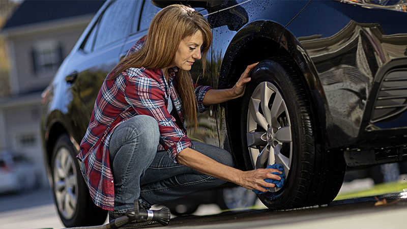 a woman washing a car wheel
