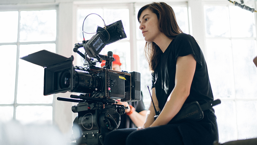 woman sitting behind a camera on a movie set