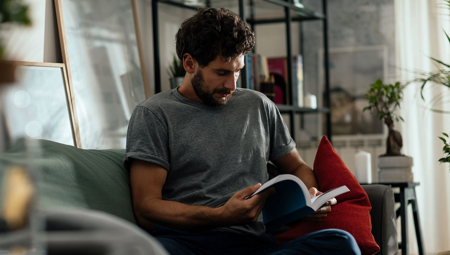 man sitting in his living room reading a book