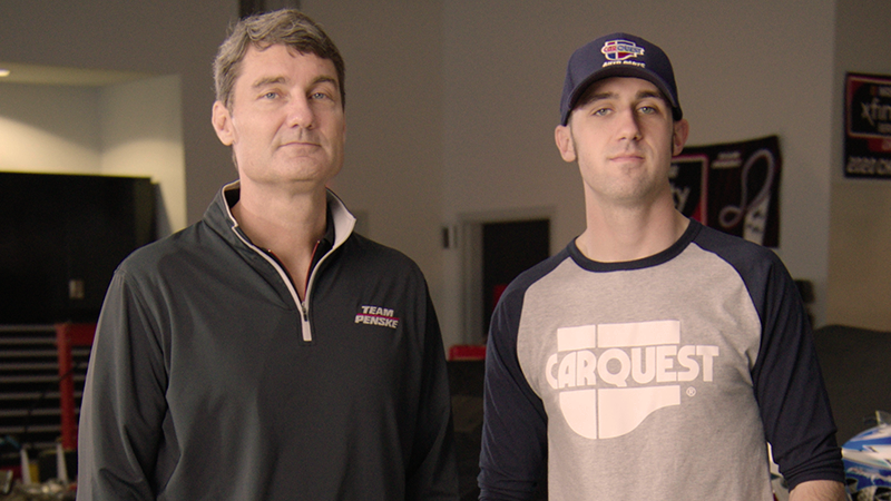 Austin Cindric stands with his father inn the garage