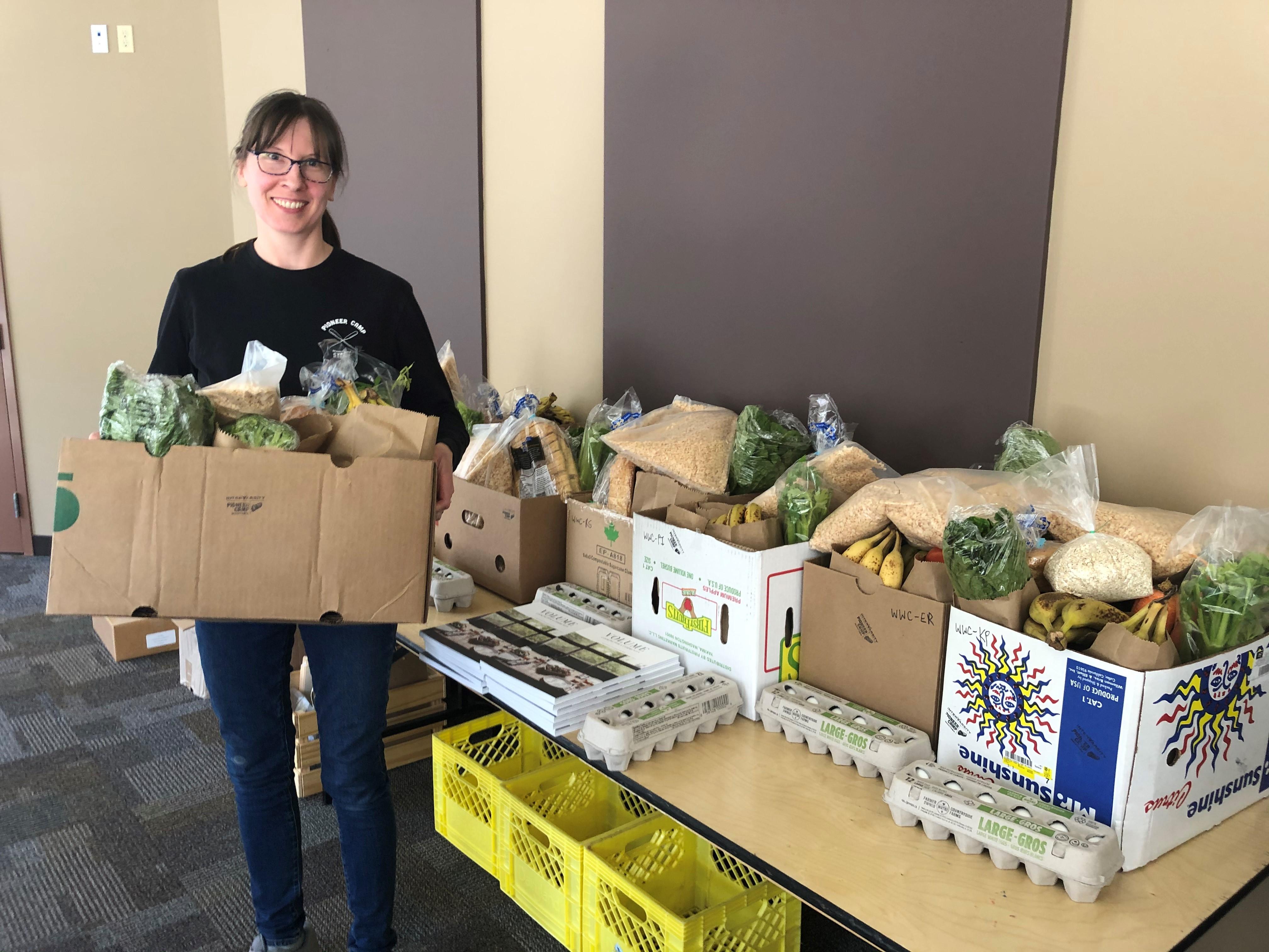 A volunteer at InterVarsity Pioneer Camp in Winnipeg, MB preparing rescued food for redistribution.