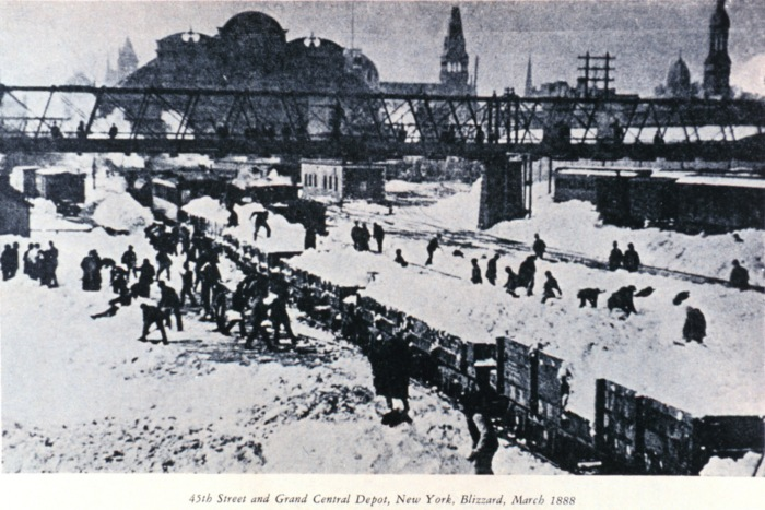 Workers clearing snow along train tracks.