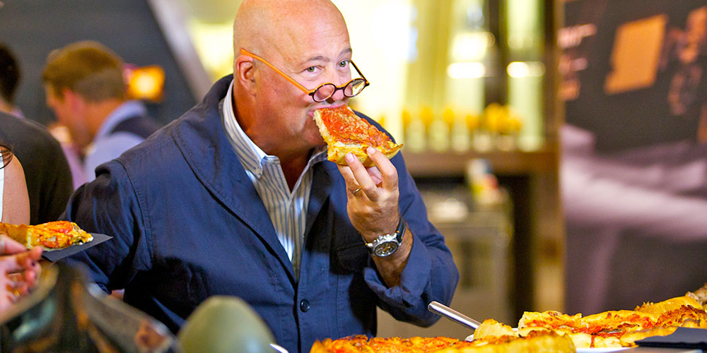 Zimmern bites into a deep-dish slice, even though he prefers New York style. (Photo: David Miller)