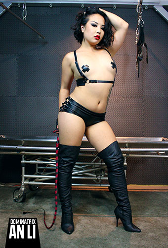 Leather fetishist An Li in nipple pasties/tape, leather BDSM harness, black thigh high leather boots, holding her single tail whip