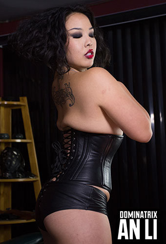 Los Angeles Asian Dominatrix An Li in fetish black leather corset, black leather booty shorts, and classic femme fatale red lips showing off Her back tattoo