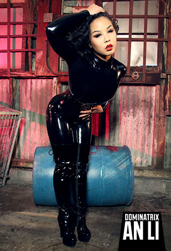 Shine and polish Domina An Li in her sleek black latex catsuit, heavy rubber corset, thigh high boots