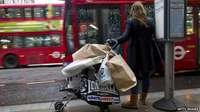 A woman waiting for a bus with a pushchair full of shopping