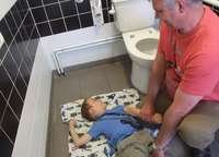 Alfie being changed on the floor of a toilet
