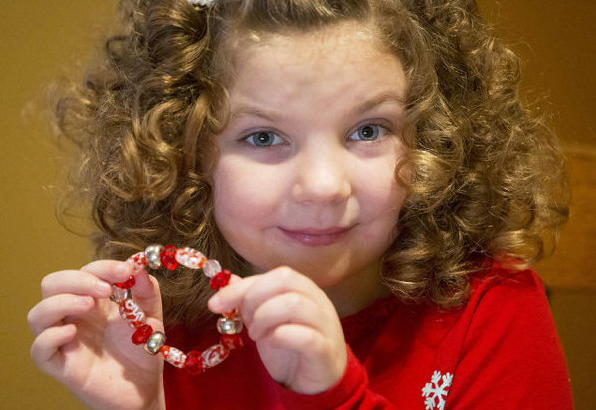 Olivia Heaston shows off a bracelet she made at her home. Olivia is making bracelets to raise money so her family can adopt 2 children from Bulgaria. (Dec. 18, 2012)