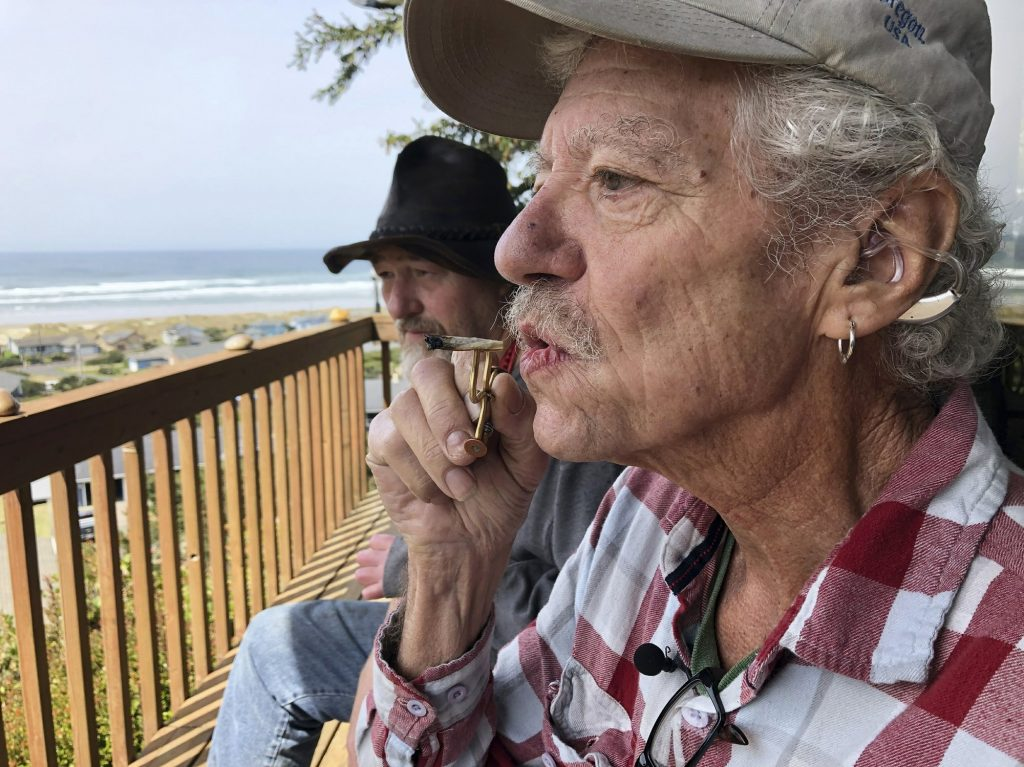 In this April 25, 2019, photo, two-time cancer survivor and medical marijuana cardholder Bill Blazina, 73, smokes a marijuana joint on the deck of his neighbor's home in Waldport, Ore. Blazina also uses a high-potency marijuana oil as a medical marijuana patient but he can't afford it at a recreational marijuana store. Blazina has learned how to make his own oil in a rice cooker after watching online videos. (AP Photo/Gillian Flaccus)