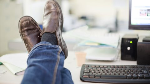 Resting at office: human legs on desk