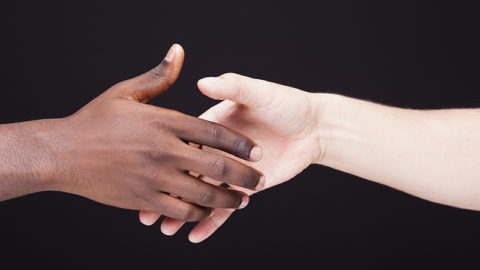 African and a caucasian man shaking hands over black background