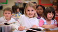 Girl smiling while working on homework in classroom