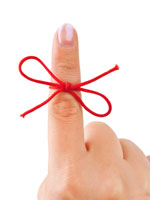 Red string tied on a finger