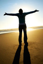 man basking in sun with hands outstretched