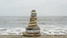 pile of pebbles stacked on a sea wall near the oceon
