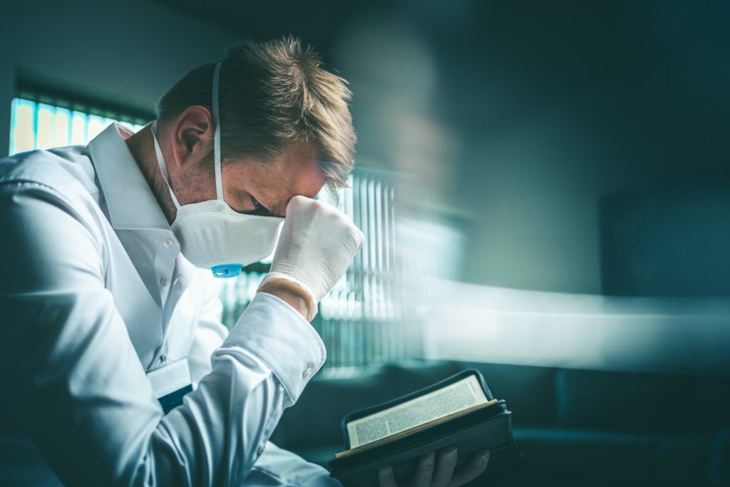 Man reading Bible with mask on