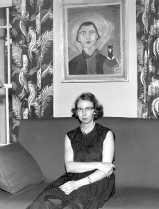 Flannery O'Connor seated beneath her iconic self-portrait
