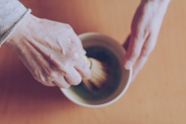 Whisking matcha with a traditional bamboo chasen