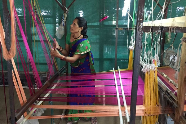 A woman adjusting her loom in India