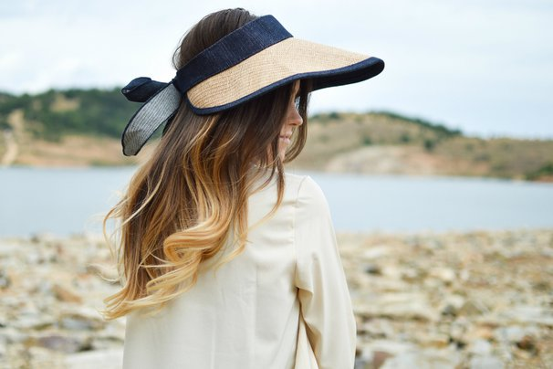 Woman in straw hat looks out across the water
