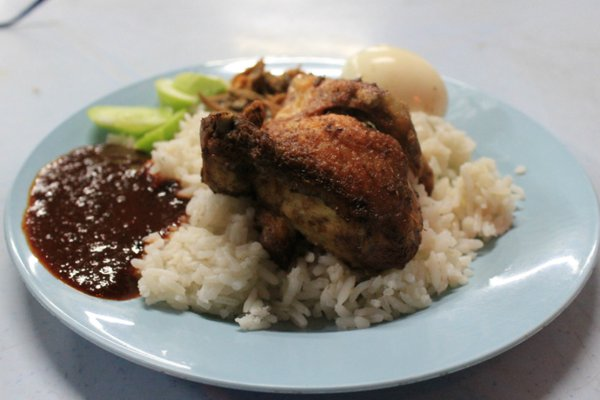 Traditional Nasi Lemak is a deep-fried chicken drumstick with a fried egg, chili paste, sliced cucumber, fried anchovies and peanuts